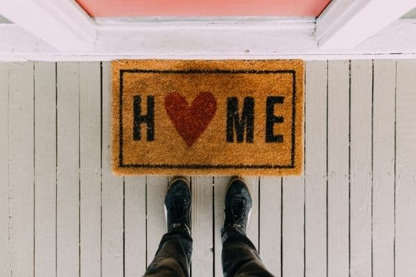 Here is a front porch that has a door mat that says home with a heart for the o.