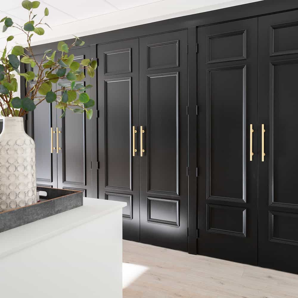 A wall of cabinetry with doors that are painted jet black and have gold oversized door handles.