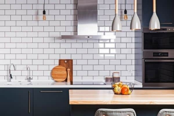This kitchen has navy blue cabinets, white countertops and white subway tile backsplash.