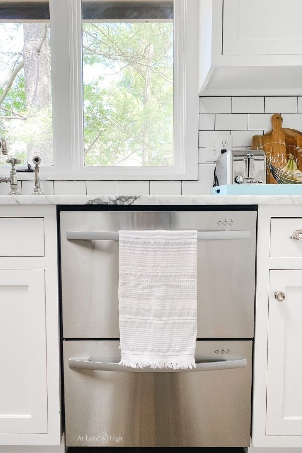 This shows a neutral striped dish towel hanging from my dishwasher in my white kitchen.