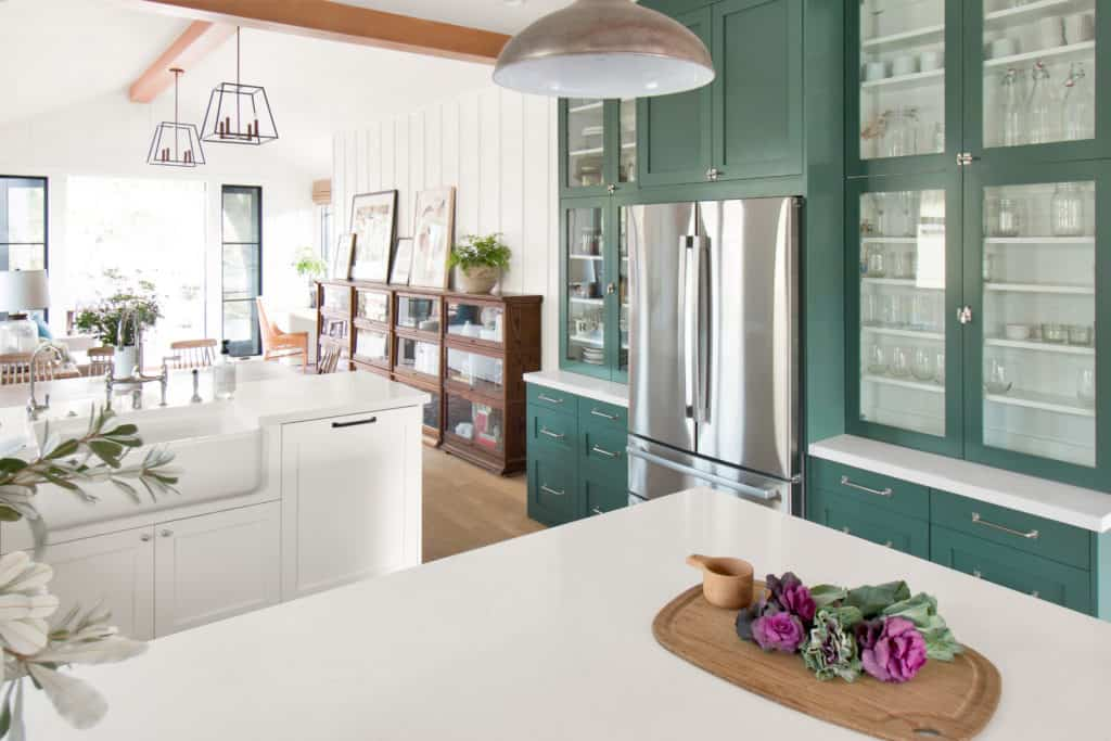 A kitchen with white counter tops, stainless appliances and lafayette green on the cabinetry.