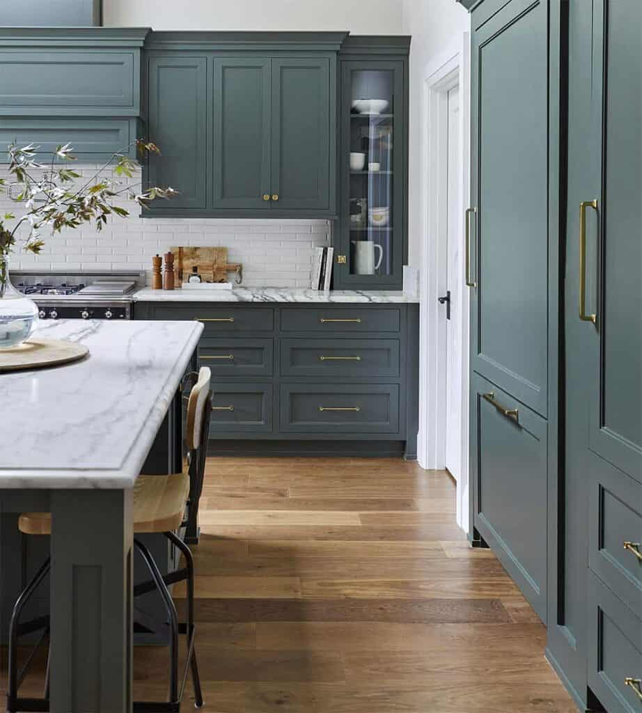 A kitchen with white walls, white subway backsplash and Pewter Green on the cabinetry with gold hardware.