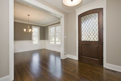 An entry way with wood floors, white trim and a beautiful wood door.