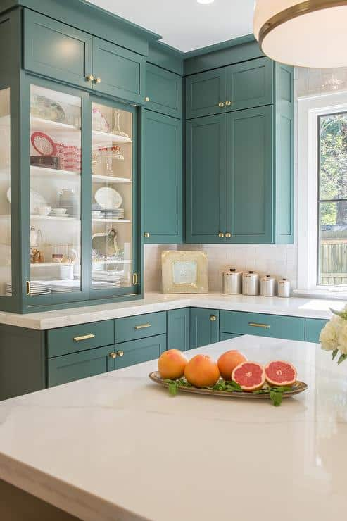 Tarrytown Green on wall cabinets with gold hardware and white marble cabinets.