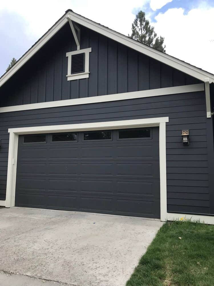 The exterior of a home with wrought iron on the siding and garage doors with white trim.