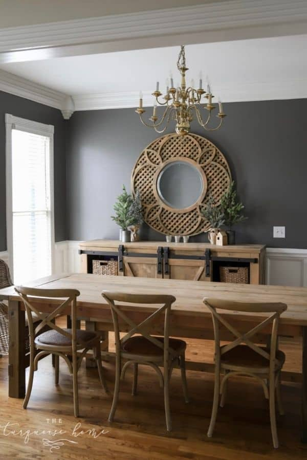Benjamin Moore Kendal Charcoal paint on the top two thirds of the walls in a dining room with white wainscoting and wood furniture.