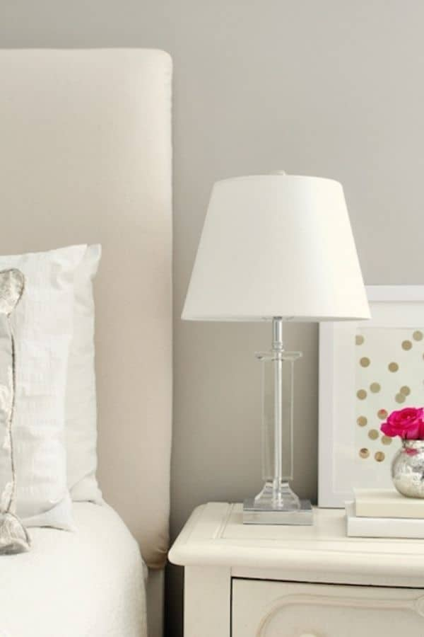 A bedroom painted in Amazing Gray with the bed and furniture all neutral creams.