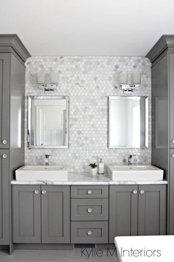 Benjamin Moore Chelsea Gray paint on bathroom cabinets with crystal knobs and carrera marble mosaic tile on the wall behind the white sinks.