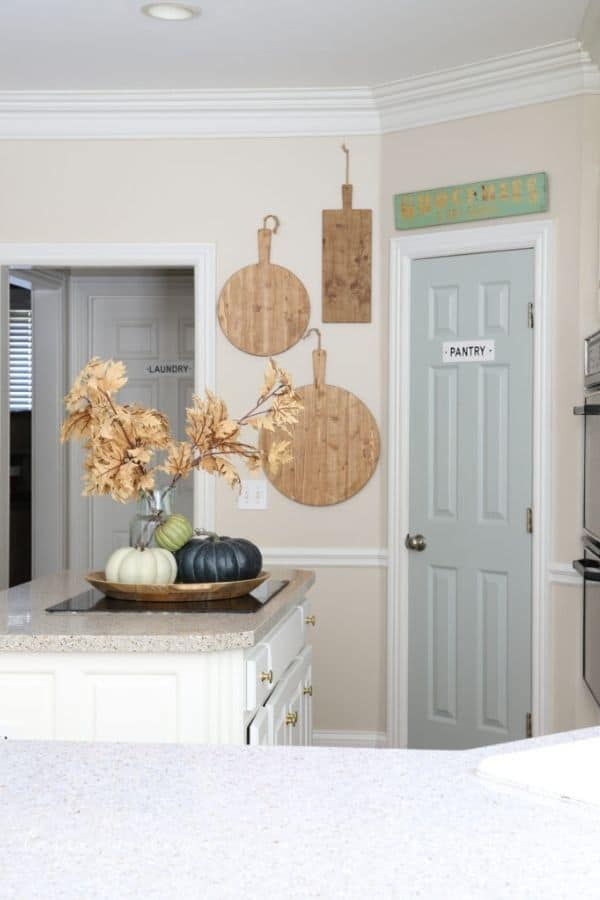 A kitchen with beige walls and the pantry door painted in Comfort Gray.