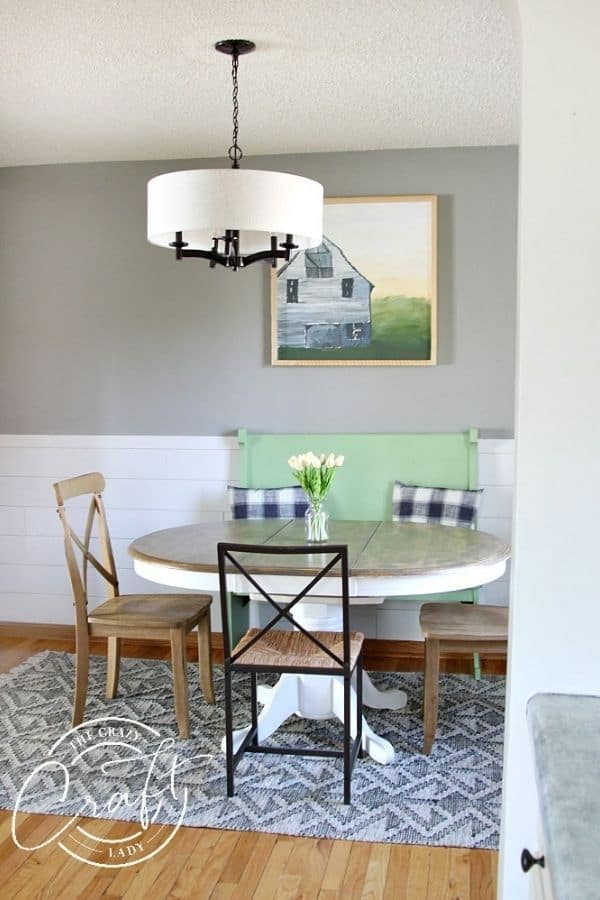A dining room that has white shiplap wainscoting and Dorian Gray on the walls above which is one of Sherwin Williams Gray Paint Colors.