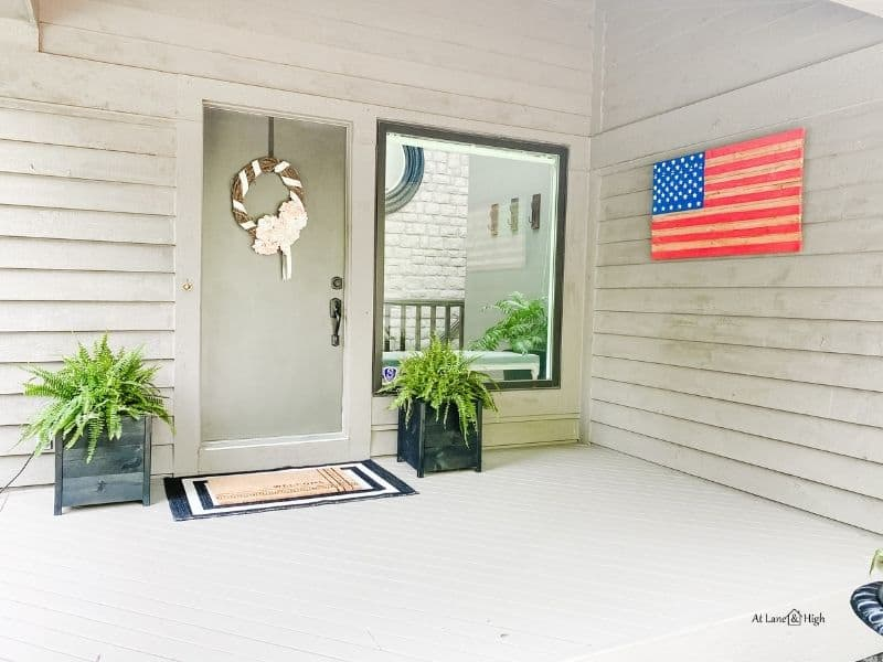 The summer front porch with layered rugs, one in black and white and the other a welcome mat.