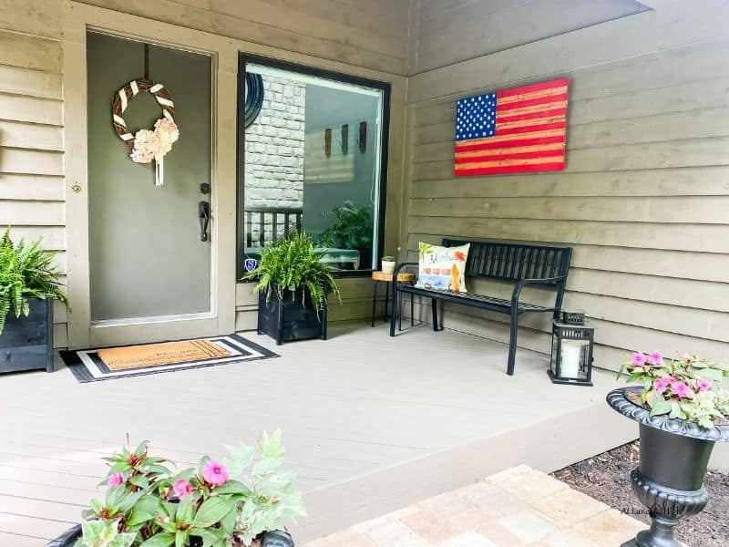 Front porch with lots of black accents and a diy wooden american flag on the garage wall.