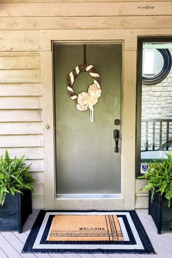The front door with layered rugs, a diy hydrangea wreath and ferns flanking the front door.