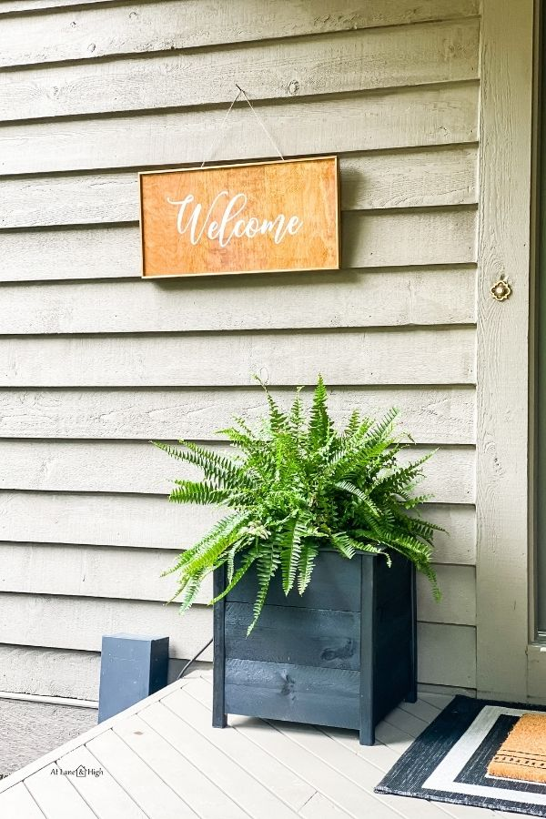 The black porch planter with a fern and a welcome sign.