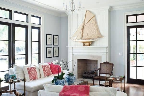 Benjamin Moore Wickham Gray on the walls in a coastal inspired family room with a fireplace that has vertical shiplap above and a large sail boat on the mantel.