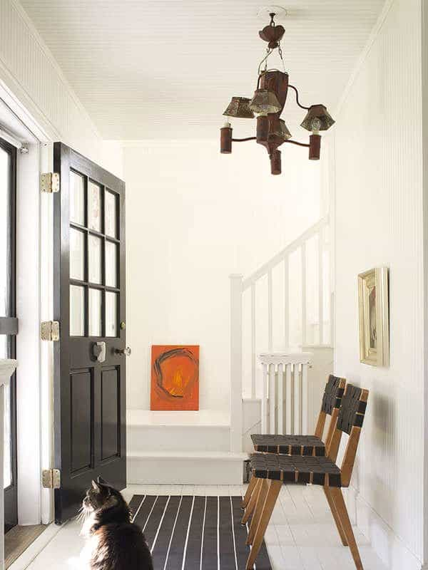 This entryway has. white dove on the walls and lots of black accents in the door and chairs.