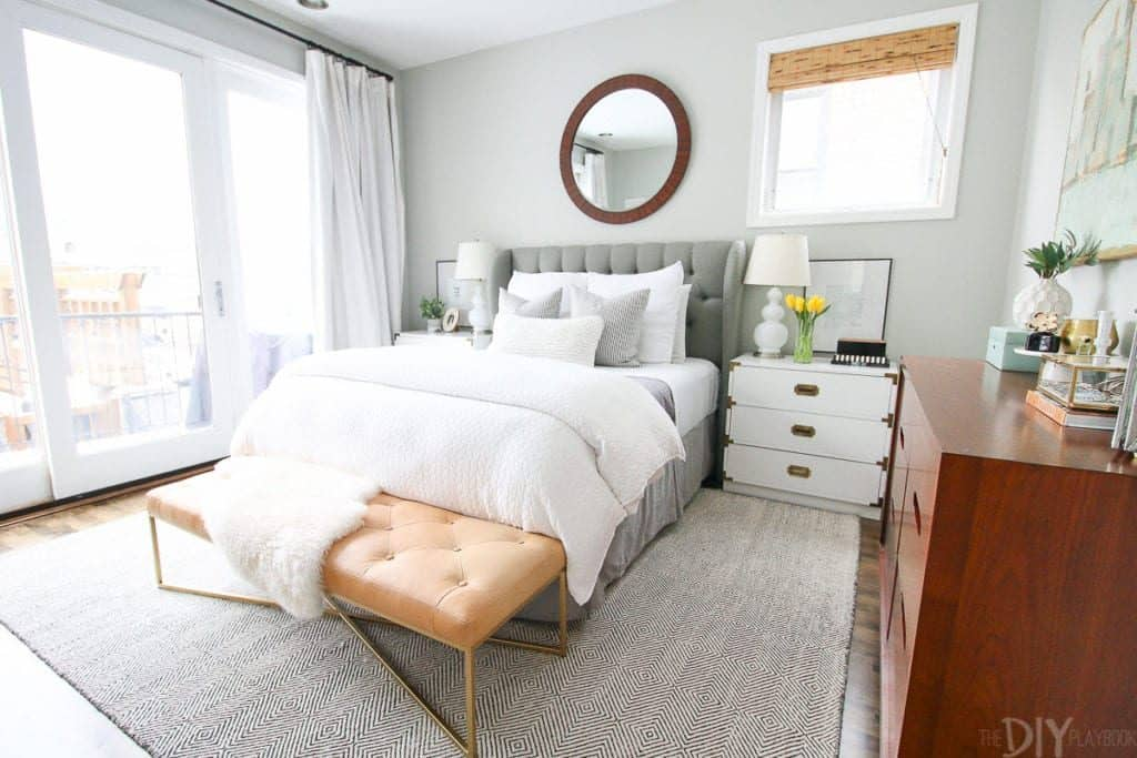 Benjamin Moore Gray Owl on the walls of a bedroom that has huge sliding glass doors, a gray upholstered bed with white linens.