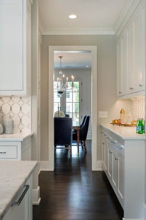 This kitchen has Gray Owl on the cabinets with silver hardware, dark brown floors and the backsplash is a circle motif in white a d gray.