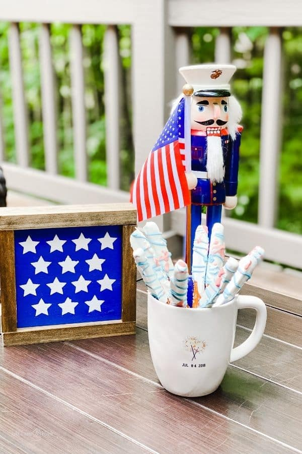 A farmhouse sign with with stars on it next to a Marine nutcracker and chocolate covered pretzel rods.