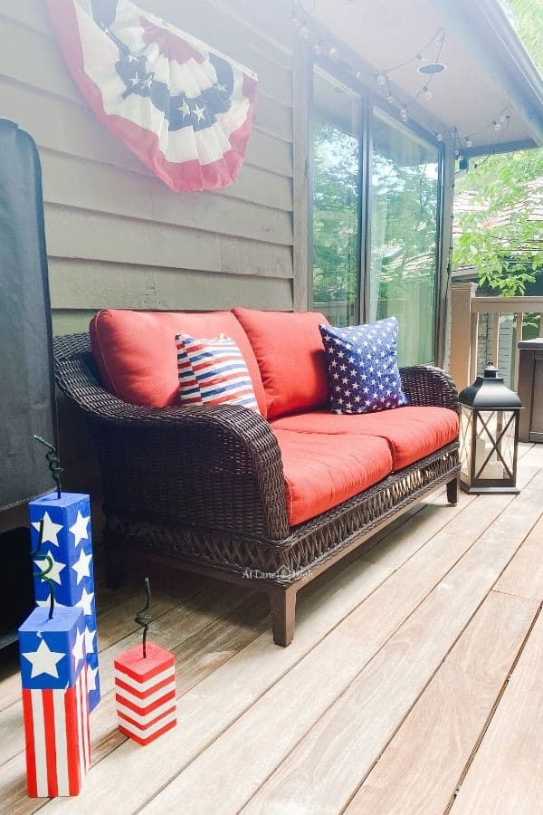 The couch with two pillows, one stars the other stripes, bunting hang on the wall above and DIY wood firecrackers on the floor next to the couch.
