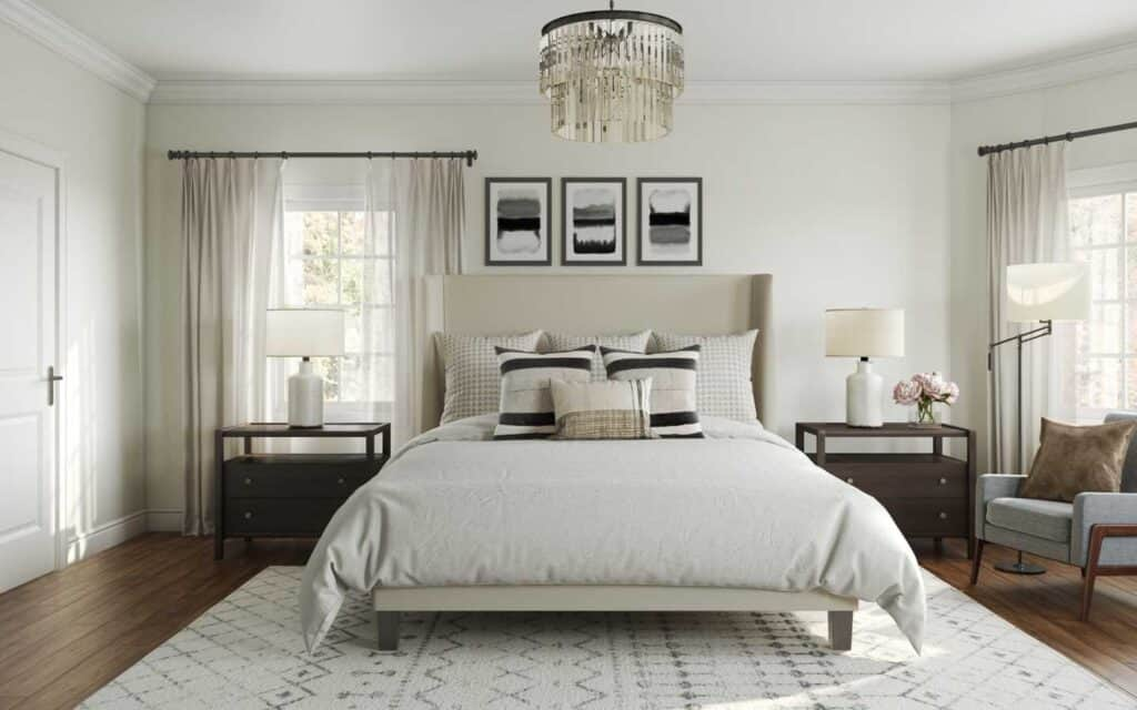 This neutral bedroom has shades of greige, a fancy crystal chandelier and hardwood floors.