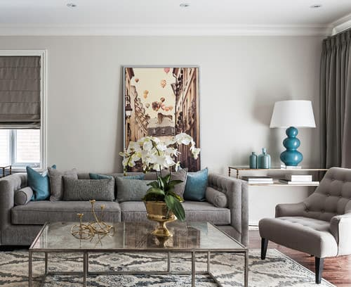 This living room has dark gray furniture and window coverings with pops of teal in the pillows and lamps.