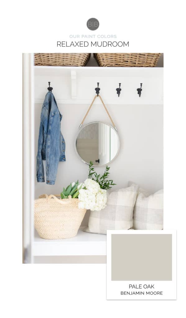 This mudroom has Pale Oak on the walls with a white bench, black coat hooks and a round mirror hanging.