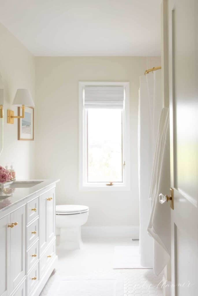 White Dove on cabinets and trim in a bathroom with very light walls and white tile floor.