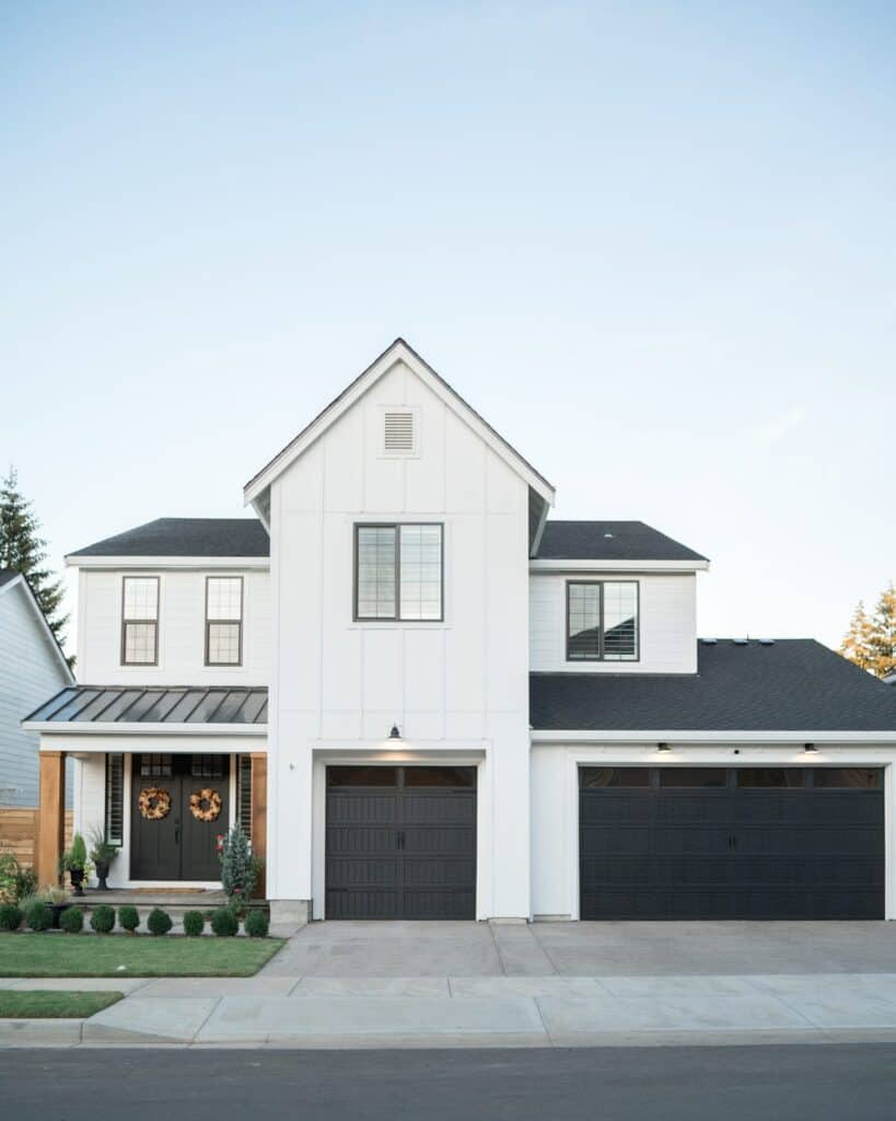 A farmhouse style home with the exterior painted in Pure white with black front door and garage doors.