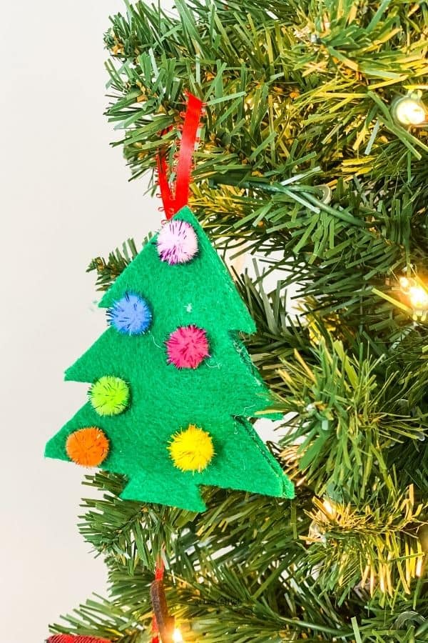 The finished felt tree with pom-poms hanging on a Christmas tree.