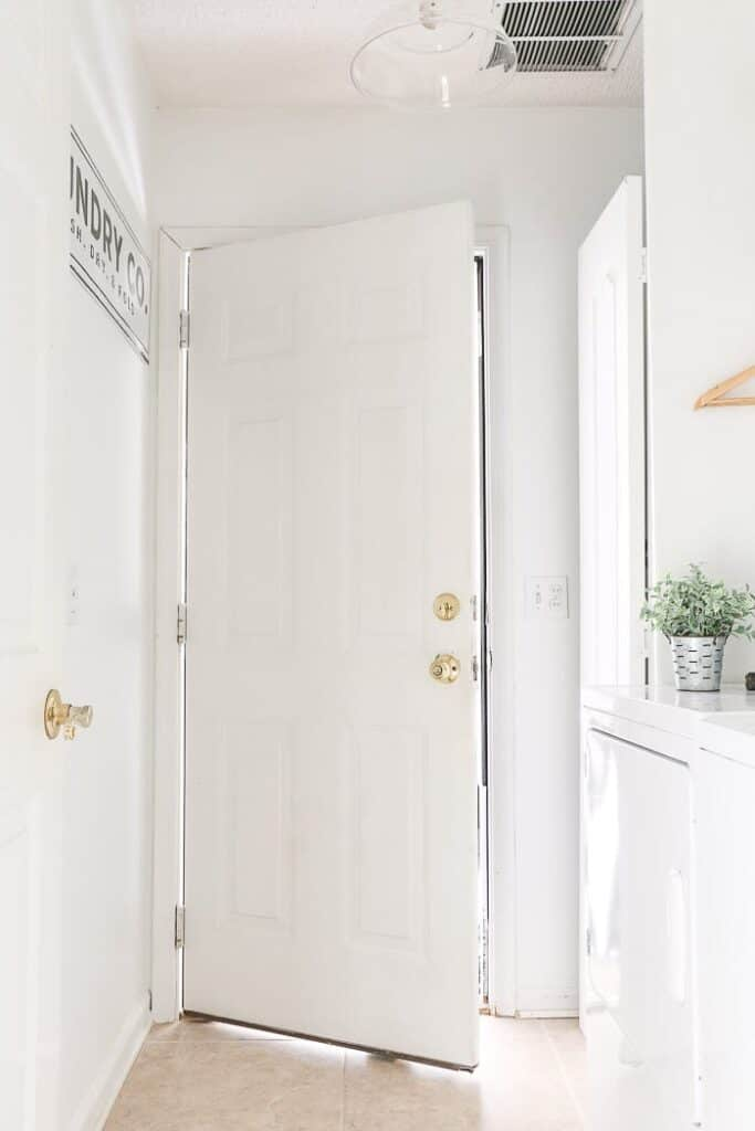 A bright laundry room painted in Pure white with white appliances and a plant on the dryer.