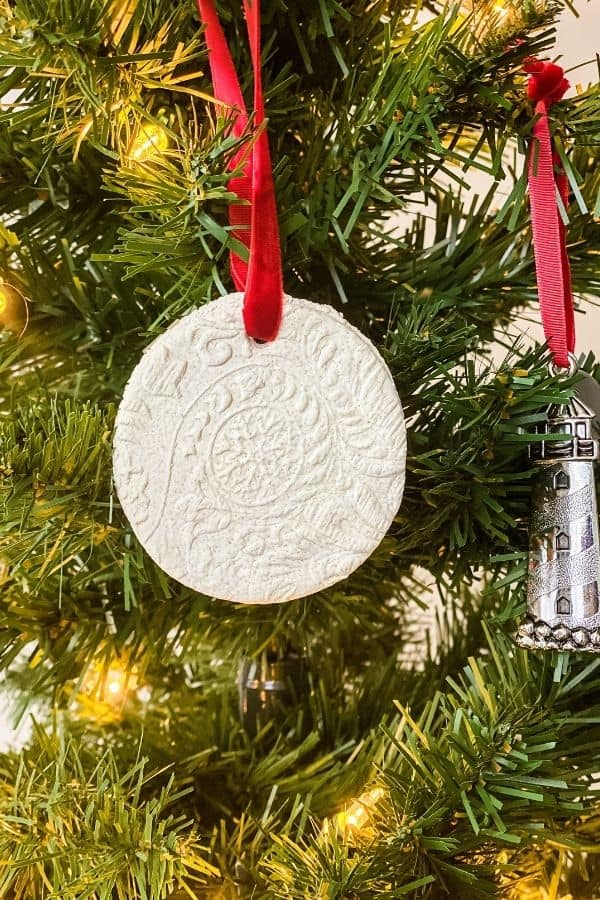 A salt dough ornament hanging on a Christmas tree with a red ribbon.