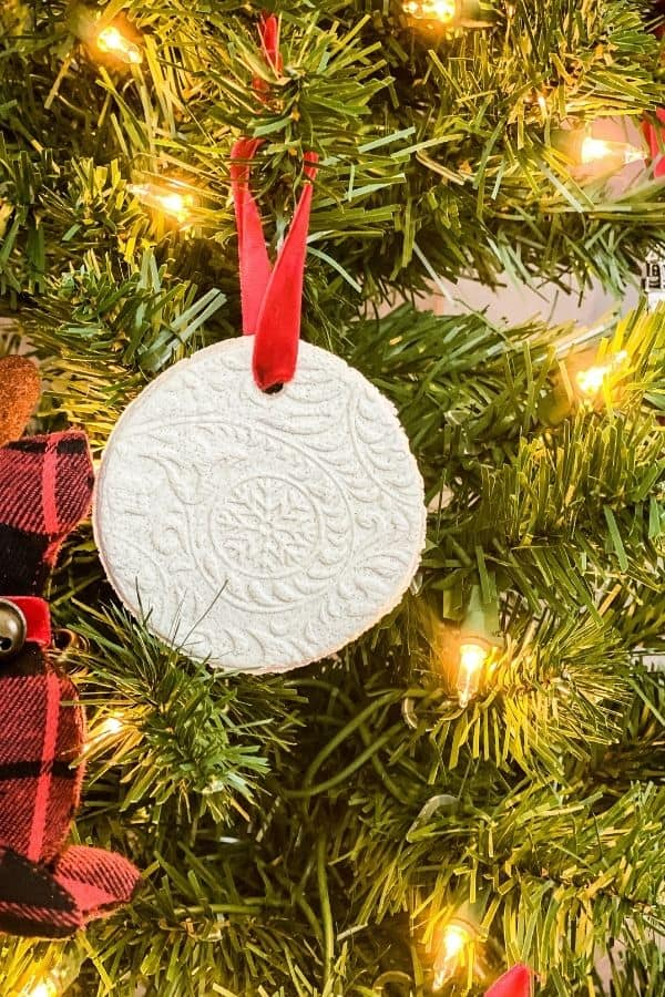Salt dough ornament hanging on a Christmas tree with a red ribbon.