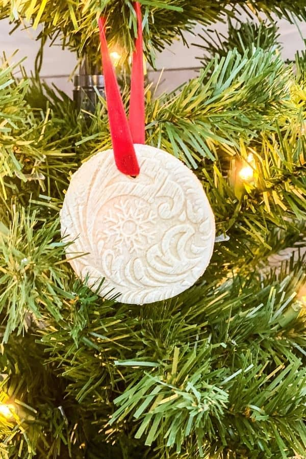 Another finished salt dough ornament hanging on a Christmas tree with a red ribbon.