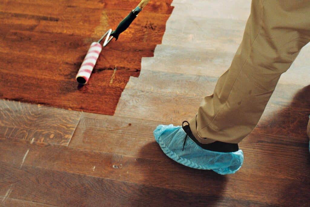Someone with beige pants and black shoes with booties over them is staining hardwood floors a pretty red-brown color.