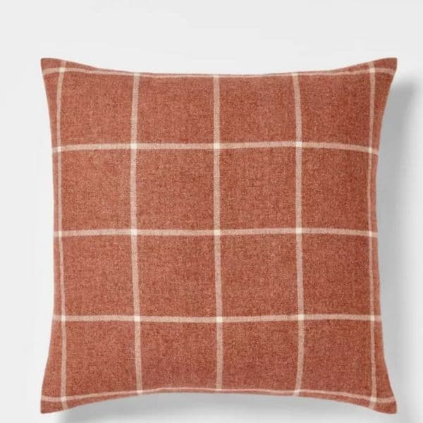 A windowpane pillow in a rust color with cream white.