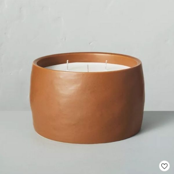 A three wick candle with a cognac colored container that smells like harvest.