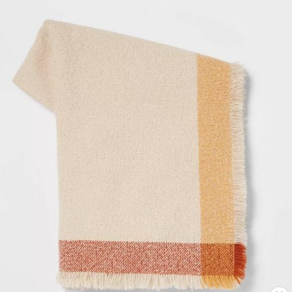 A lightweight throw blanket with a stripe in rust and yellow.