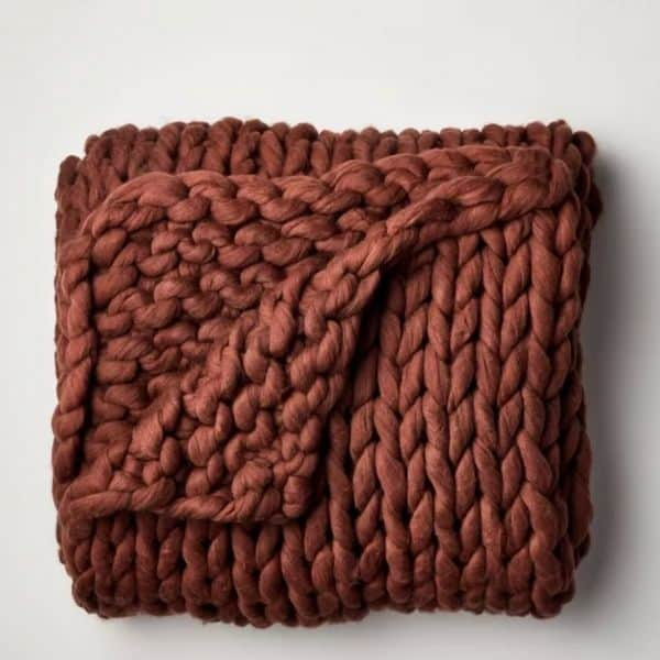 This is a cable knit throw blanket in a rust color.
