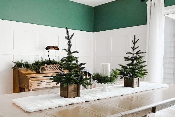 White DIY board and batten with a blue green paint color above  all decorated for Winter with garland, evergreen trees and white decor.