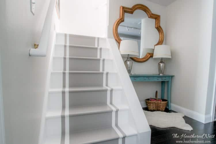 A stairwell that has been painted white with a gray painted runner in the center.