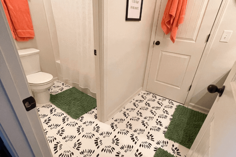A bathroom with painted floor tile and a stencil in black and white with green bath rugs and orange towels.