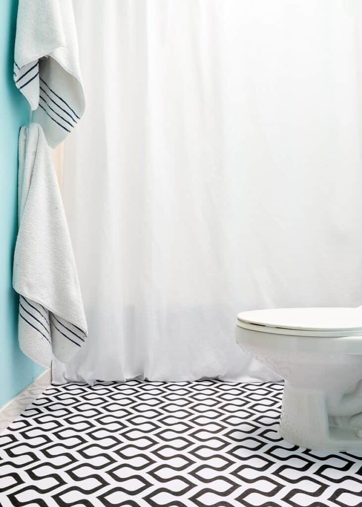 A black and white pattern wallpaper on the floors with light blue walls and a white shower curtain.