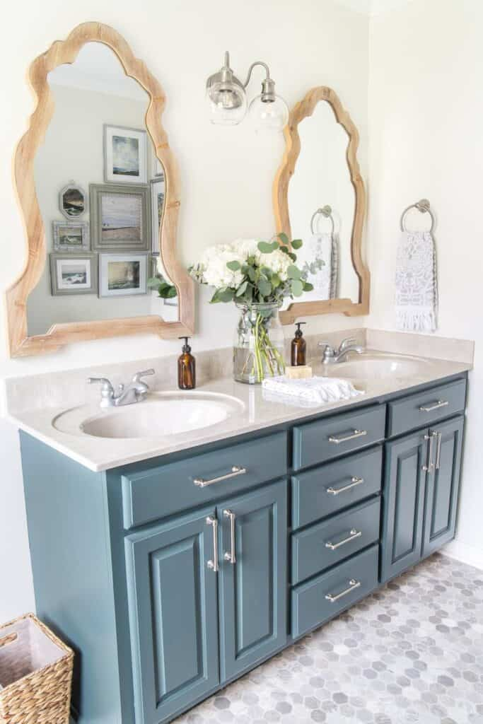 A bathroom with a blue painted vanity, white counters and gray and white marble looking vinyl floors in a hexagon shape.