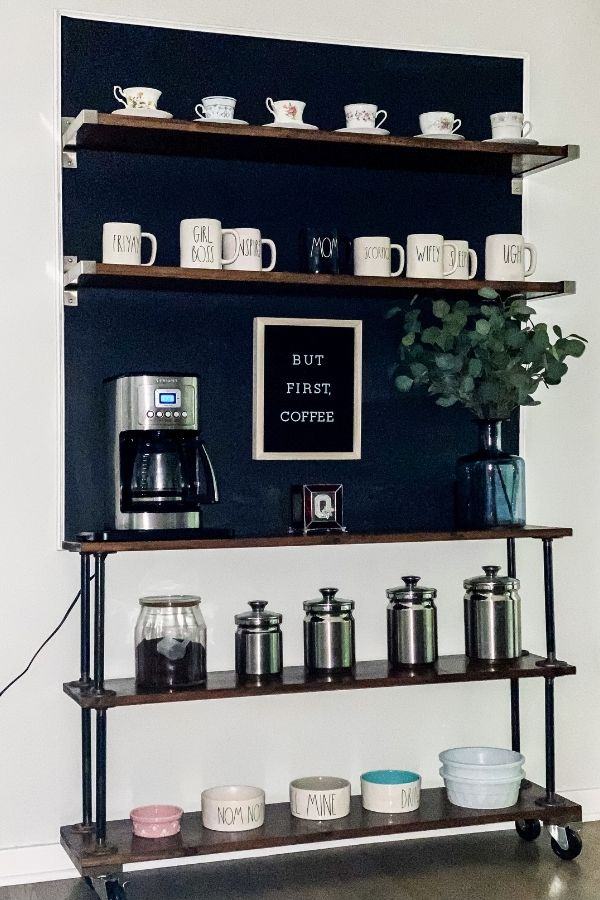 The finished industrial pipe shelves with a chalkboard above that has floating shelves too.