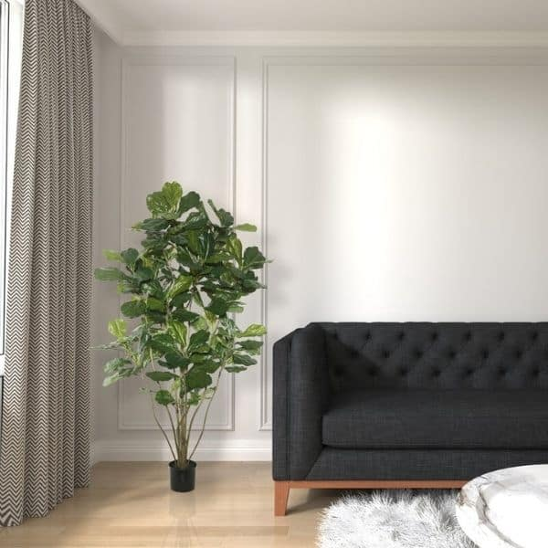 A faux fiddle leaf fig tree next to a gray couch and white walls with picture frame molding.