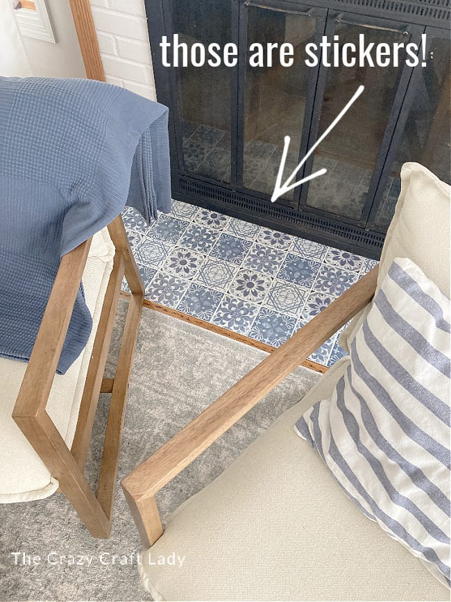 Tile stickers on a fireplace hearth in blue and white with two chairs flanking the fireplace.