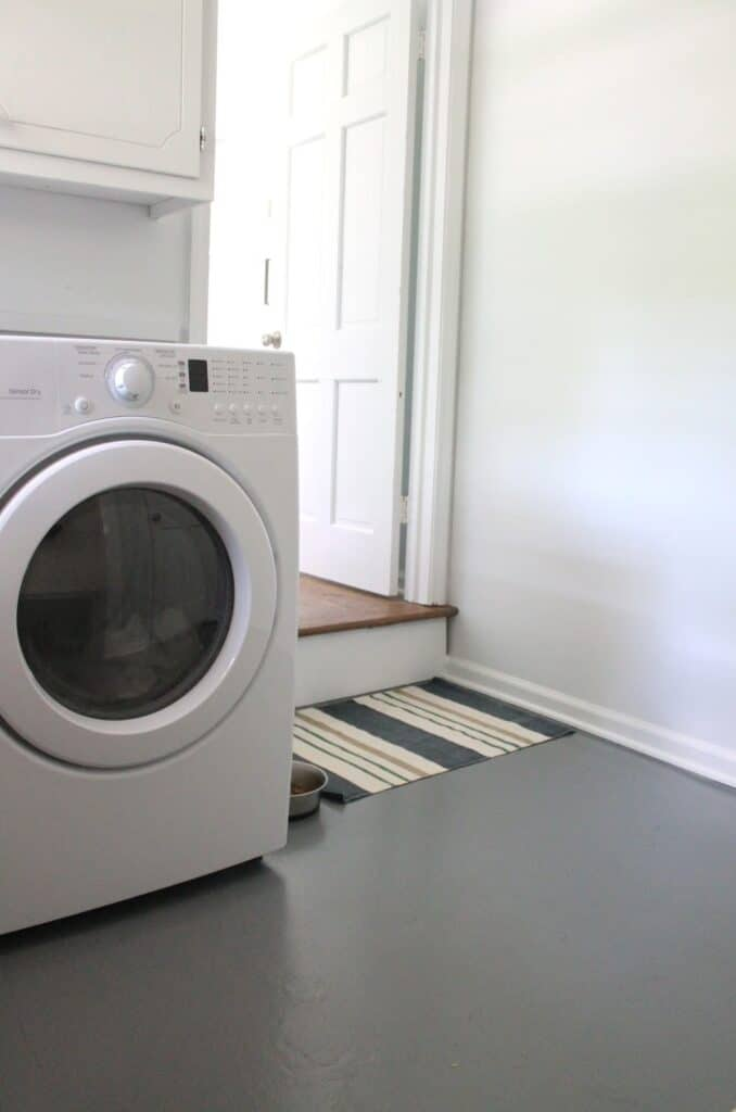 A laundry room with gray painted concrete and a blue and white striped rug.
