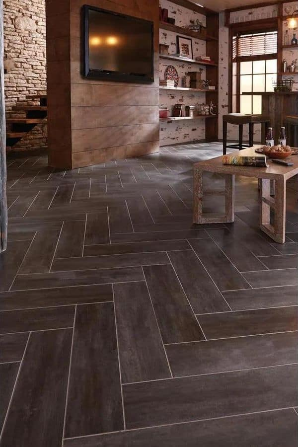 Dark gray groutable tile in a herring bone pattern in a family room with a wood coffee table.