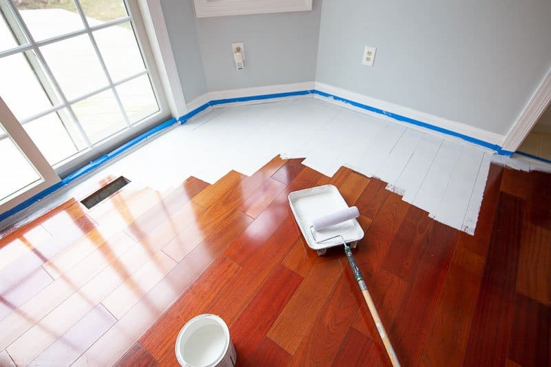 Hardwood floors in a reddish brown color being painted white.